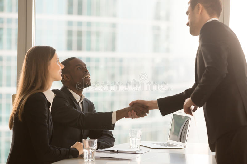 Black and white recruitment officers welcoming applicant arrived. Friendly black and white recruiters sitting at office desk shaking hands with applicant just stock images