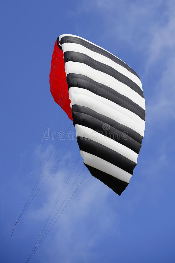 Black, white and red kite in the blue sky. The kite of a kitesurfer against an airfine blue sky stock image