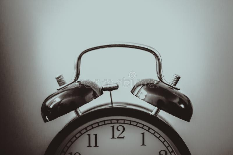 Black and white alarm clock. Black and white retro alarm clock royalty free stock image