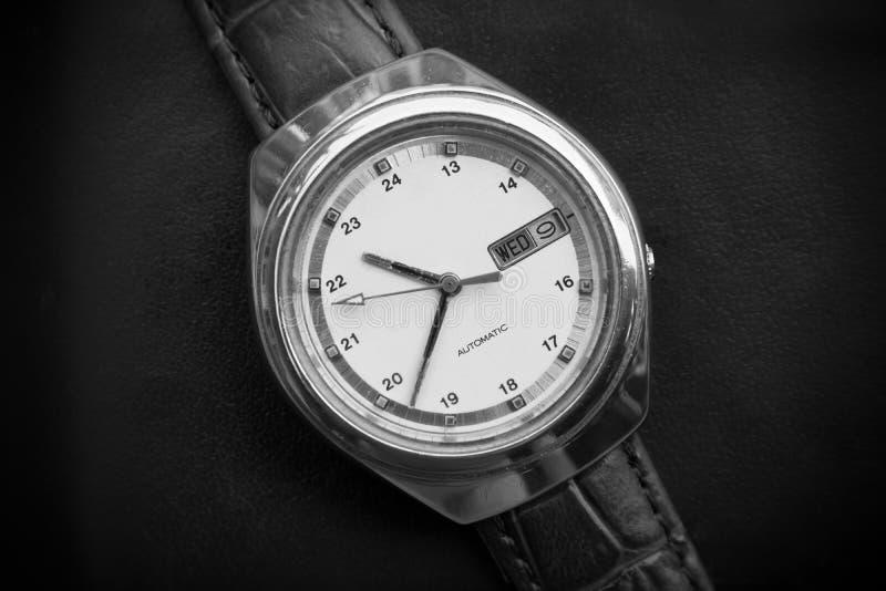 Black and white retro men wrist watch on black leather background. Old men wrist watch. On black surface stock image