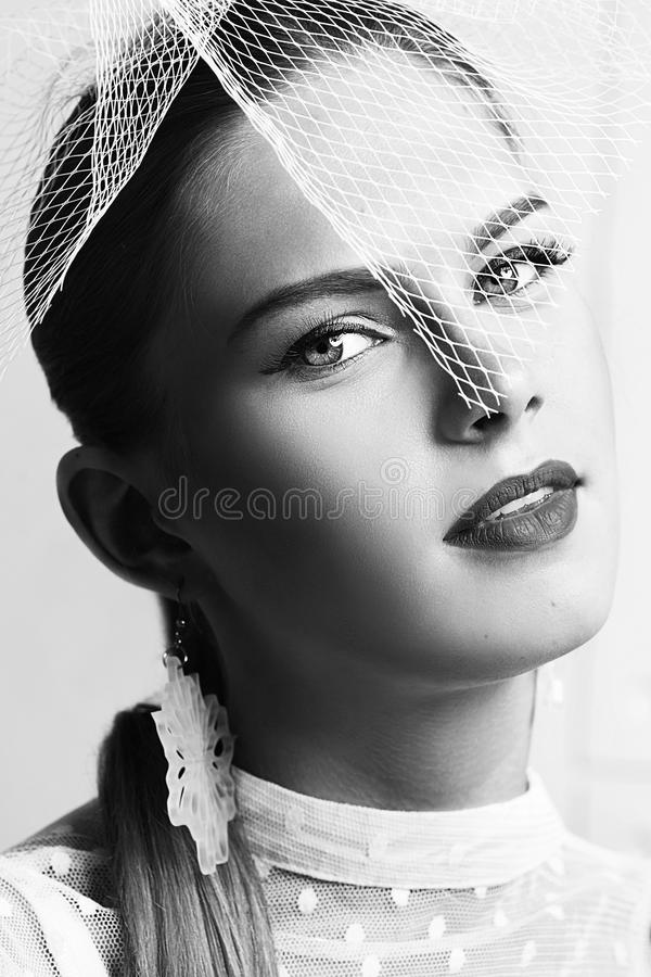 Black and white retro portrait of beautiful woman with stylish hat and elegant white dotted blouse looking forward. royalty free stock image