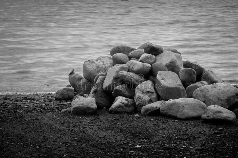 Black and White Rock Pile on Shore. Rock pile on shore in black and white royalty free stock photos