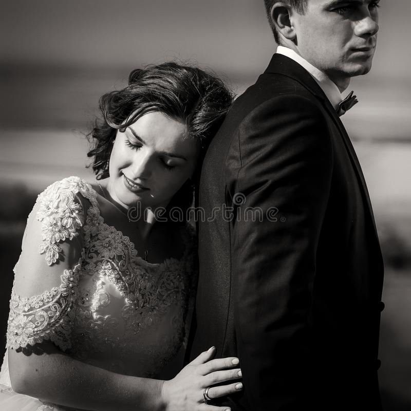 Black and white romantic portrait of the tender charming bride leaning on the back of her handsome lover. stock photography
