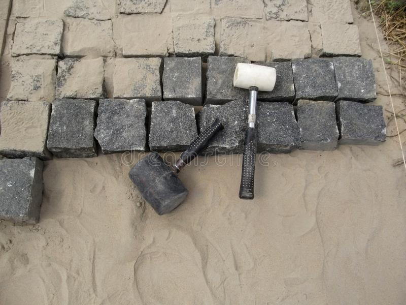 Black and white rubber Mallets lie on unfinished granite paving stones - top view. Incomplete work on laying paving slabs, the concept of landscaping of royalty free stock image