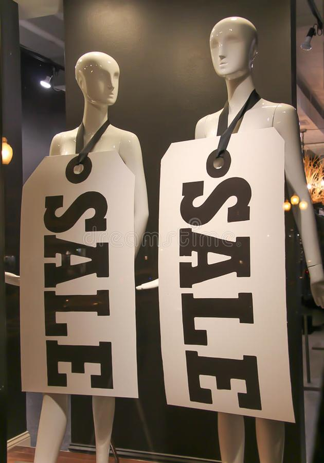 Black and white sale signs. Hung on plain white mannequins in a shop window stock photography