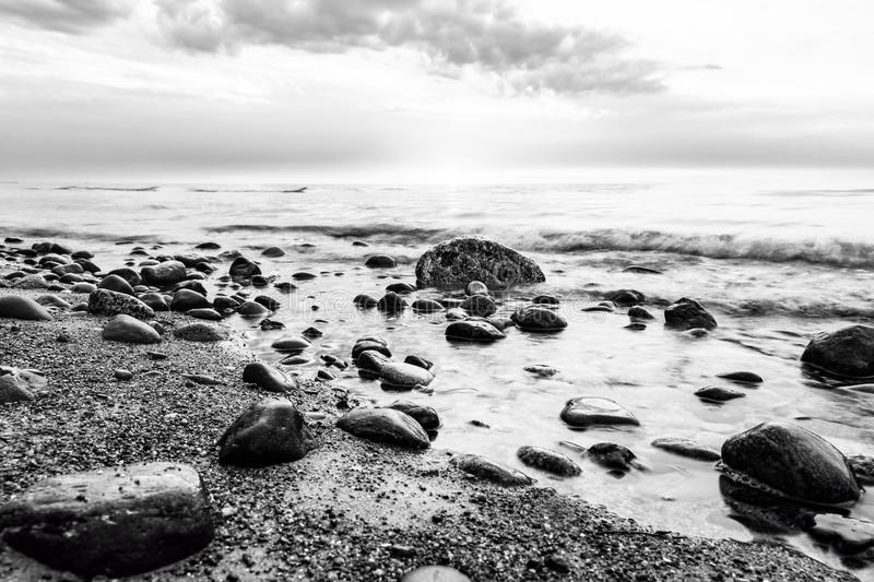 Black and white sea. Waves hitting in rocks. Wild beach royalty free stock photography