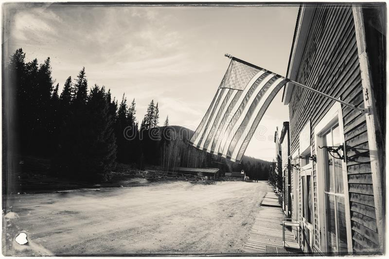 Black and White Sepia Vintage Photo of Old Western Wooden Buildings with flag of the united states. In St. Elmo Gold Mine Ghost Town in Colorado, USA hidden in stock photography