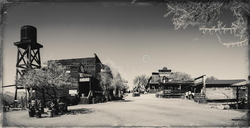 Black and White Sepia Vintage Photo of Old Western Wooden Buildings in Goldfield Gold Mine Ghost Town. In Youngsberg, Arizona, USA surrounded by cactuses royalty free stock photo