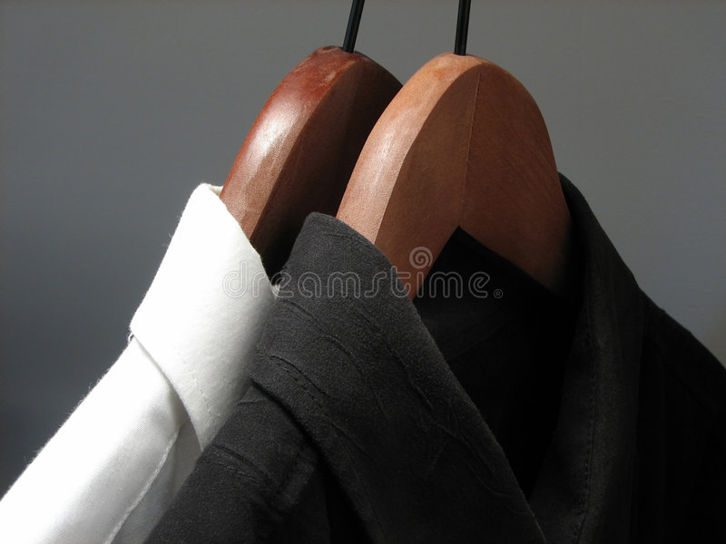 Black and white shirts on wooden hangers stock images