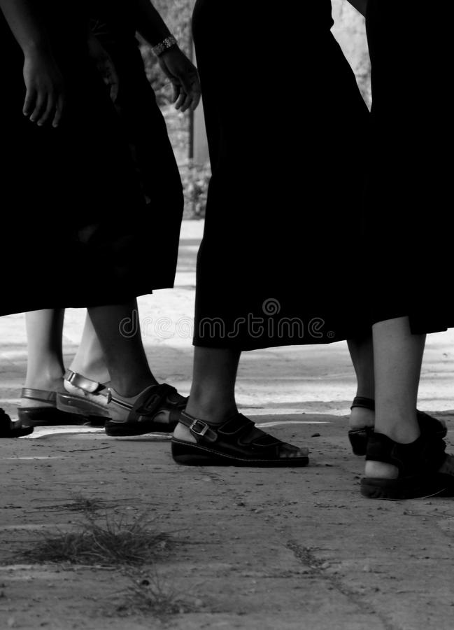Black and white shot of female legs wearing sandals and skirts royalty free stock images