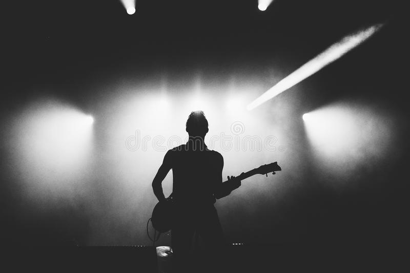 Black and white shot of guitarist silhouette in a stage backlights. Guitarist silhouette on a stage in a bright stage lights. Black and white royalty free stock photography