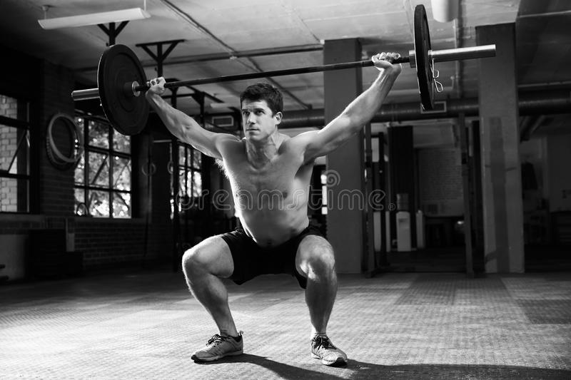 Black And White Shot Of Man In Gym Lifting Weights stock photo