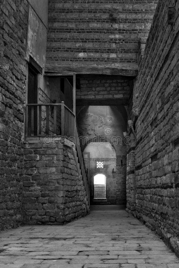 Black and white shot of old abandoned stone bricks passage surrounding Sultan Qalawun Complex, Cairo, Egypt. Black and white shot of old abandoned stone bricks stock photo