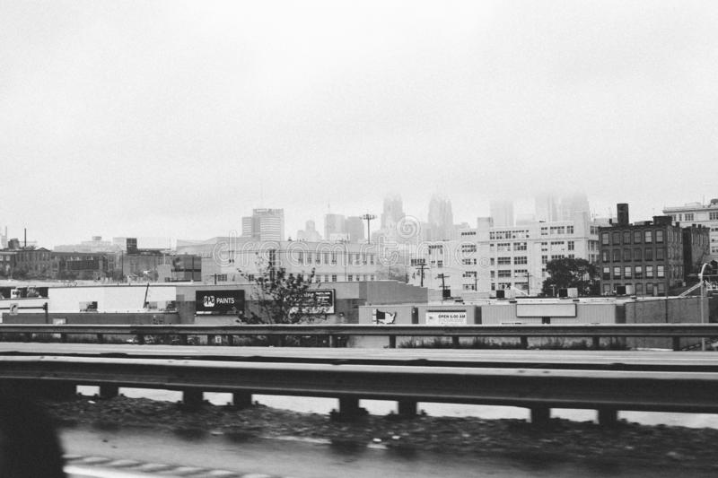Black and white shot of tall buildings across the road in the city stock photo
