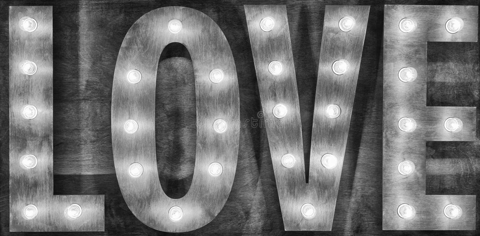 Black and white sign love light bulbs on wooden background. royalty free stock images