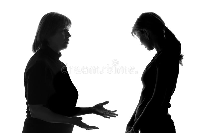 Black and white silhouette of a daughter who humbly listens to mother's words and realizes his guilt stock photography