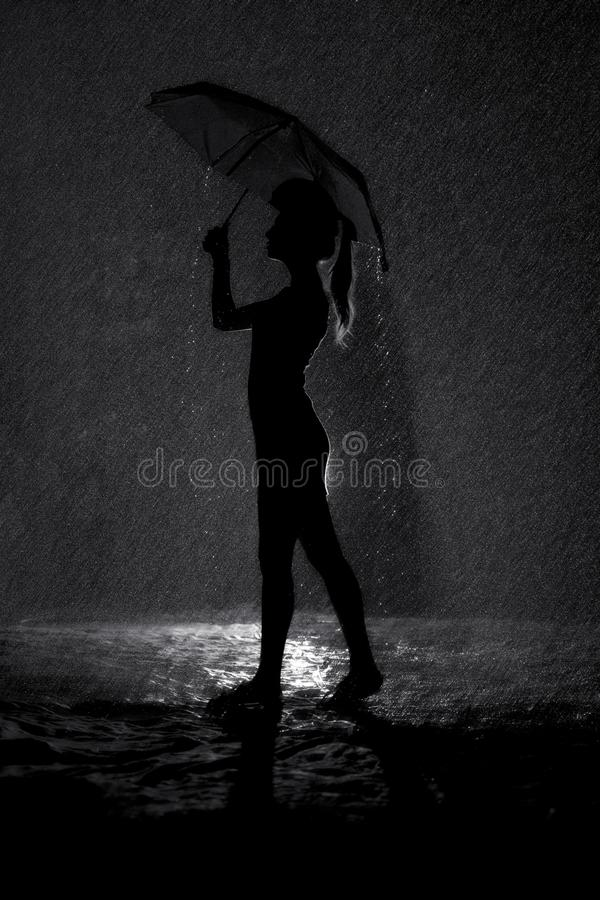 Black and white silhouette of the figure of a young girl with an umbrella in the rain, concept weather and mood royalty free stock photos