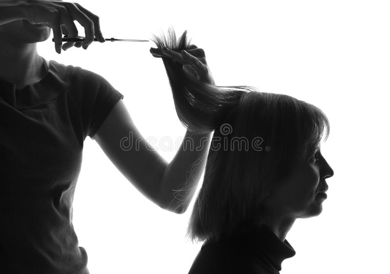 Black and white silhouette hairdresser cuts client's hair royalty free stock photography
