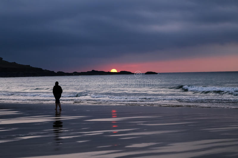 Silhouette of Man in Hoodie Walking Alone on Beach During Sunset stock image