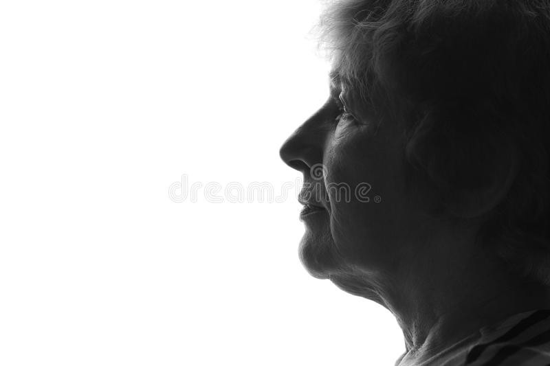 Black and white silhouette of a profile of an old woman on an isolated background. Black and white silhouette of an old woman on an isolated background royalty free stock photography