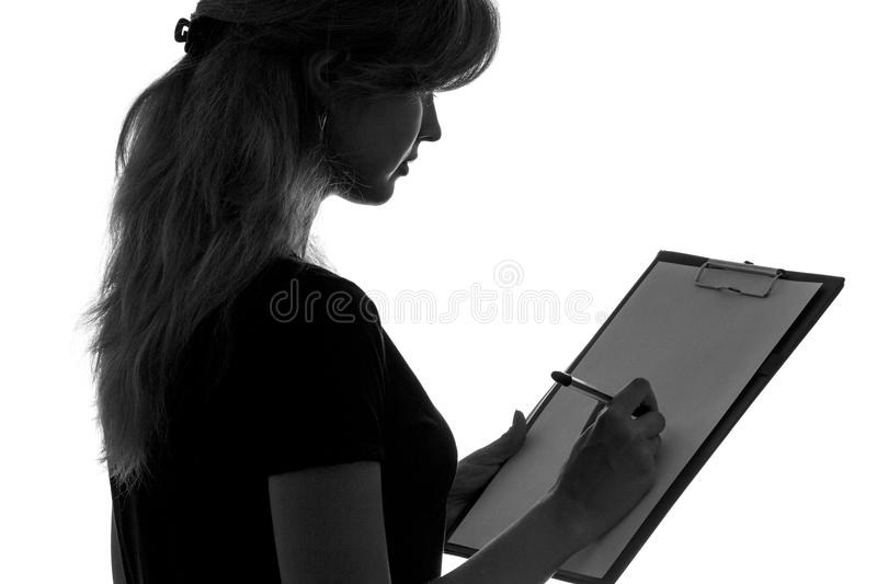 Black and white silhouette of a woman working in an office with a folder for sheets and a pen in the hands royalty free stock photography