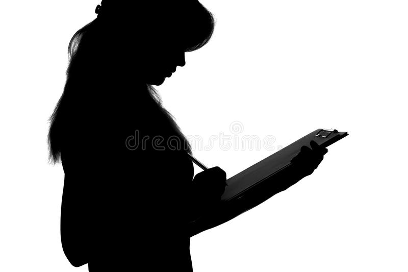 Black and white silhouette of a woman working in an office with a folder for sheets and a pen in the hands stock images