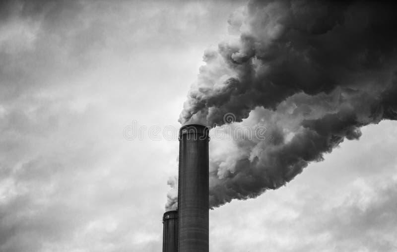 Black and White of smoking smokestacks stock photo