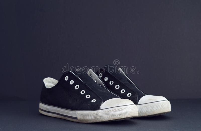 Black and White Sneakers. Over dark black background. This image is part of a large series stock photos