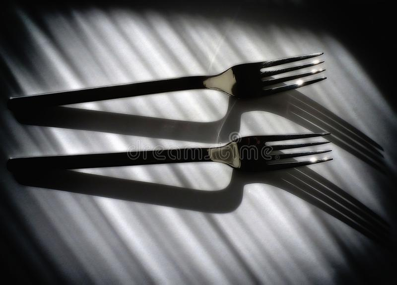 Black and white still life image with shiny chrome forks stock photos