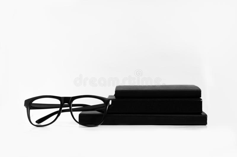 Black and white still life: opened blank notepad with linear pages, notebooks, pen, glasses, watch, cup of coffee and lipstick. stock photo