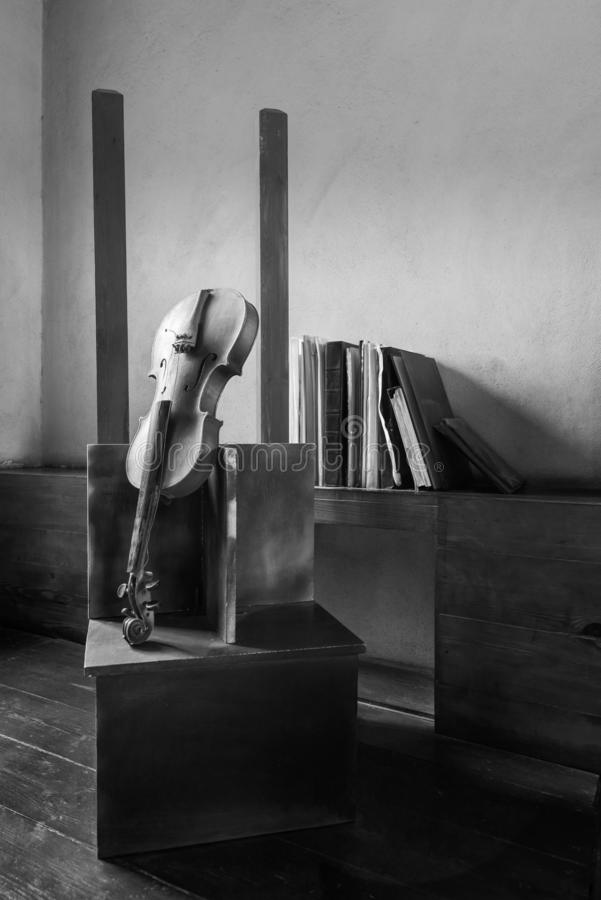 Black and white still life of broken old broken violin and vintage grunge books royalty free stock photo