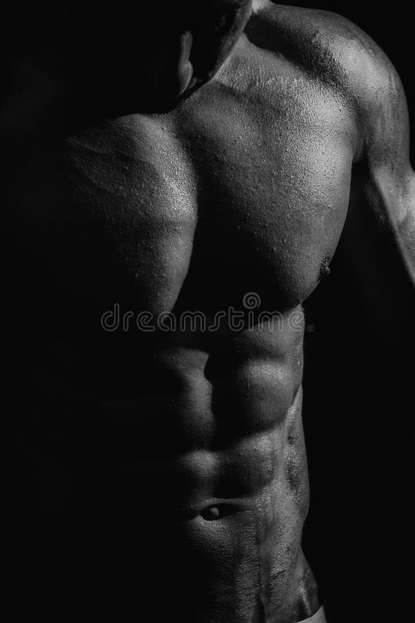 Black and white studio shoot of strong athletic man. On dark background royalty free stock images