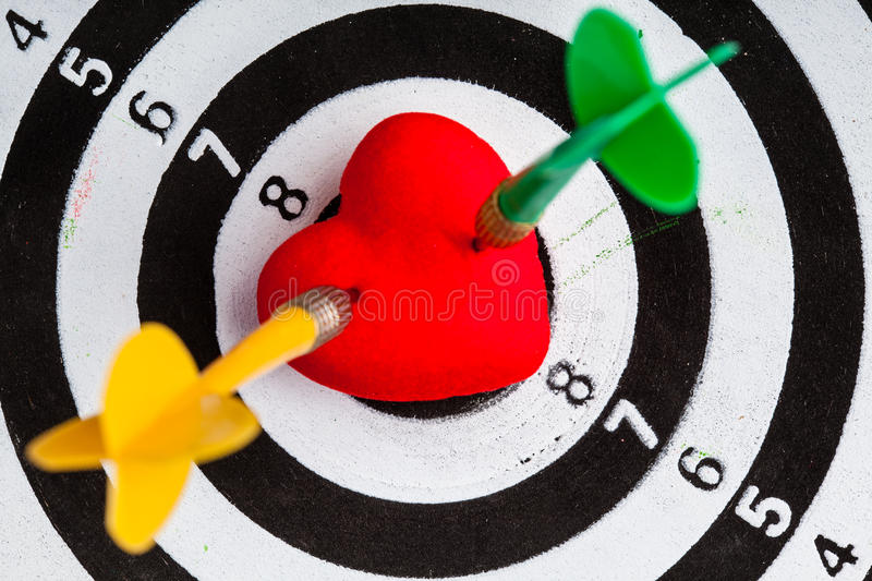 Black white target with two darts in heart love symbol as bullseye. Closeup of black and white target with two dart in red valentine heart love symbol as stock image