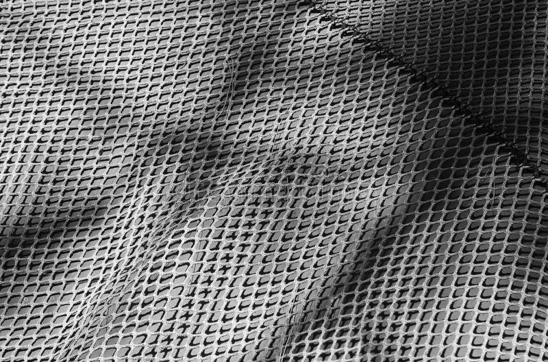 Black and white textile grid background. Light and shadow alternate on the chicken wire background stock photography