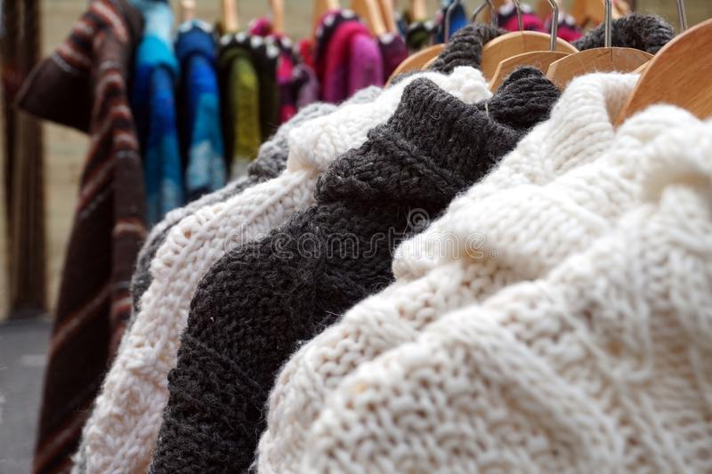Black and white thick knitted wool winter jumpers and jackets for sale on a marlet stall royalty free stock image