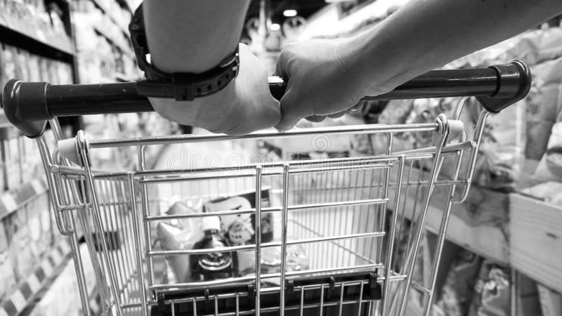 Black and white tone  man pushing a shopping cart in the supermarket royalty free stock photo