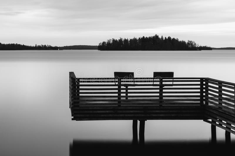 Black and white tranquil scenery of a lake with pier and two chairs. Water surface looks foggy due to long exposure