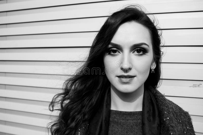 Download black and white urban portrait of lady with charming smile posing on wall background