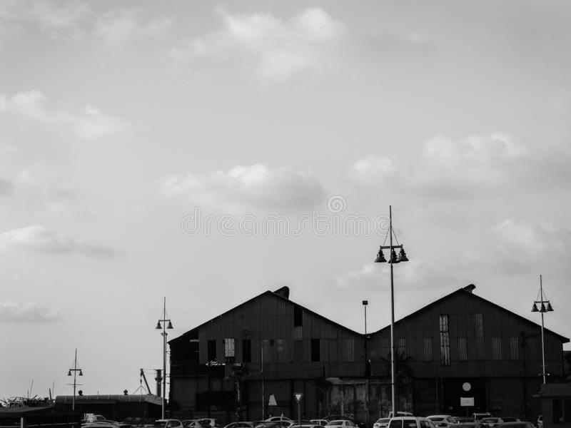 Black and white urban view of two roof tops of big buildings by the sea port, boat houses with tall city lamps in front, under stock images