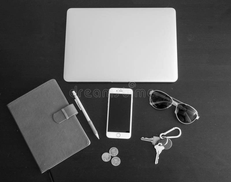 Black and white version of Business office workspace with Various items isolated on a black desk background. Including glasses, phone, keys, spare change royalty free stock image