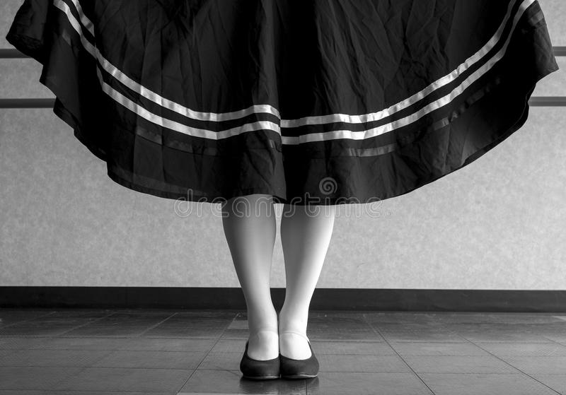 Black and white version of character ballet parallel position with skirt held. Ready to dance tradition character ballet royalty free stock photography
