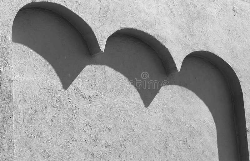Black and white version of a stucco wall with three arches casting shadows stock images