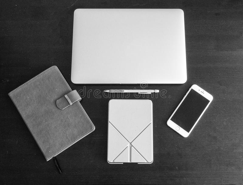 Black and white version of Student and worker desktop workspace layout including a laptop, smartphone, journal, tablet and pencil royalty free stock photography