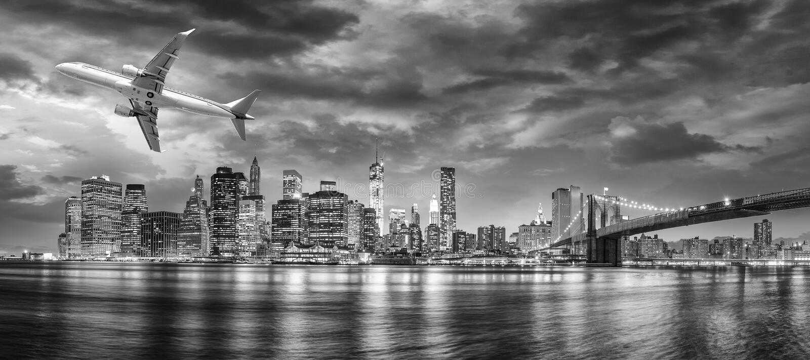 Black and white view of airplane overflying New York City royalty free stock image