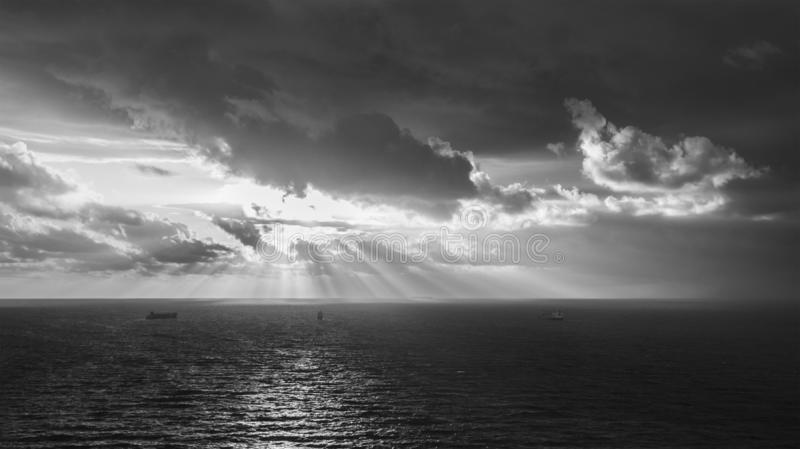 Black and white view of a stormy sky with thick dark clouds seen at sunrise. Sunbeams are seen under the hurricane sky. Large royalty free stock photography