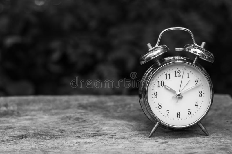 Black and White Vintage alarm clock on wooden table. Black and White Vintage alarm clock on wooden table with nature blurred background and copy space royalty free stock photo