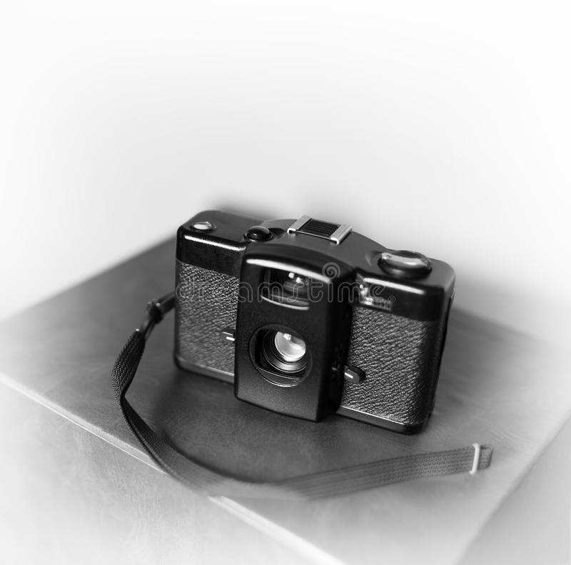 Black and white vintage camera with strap vignette bokeh background royalty free stock image