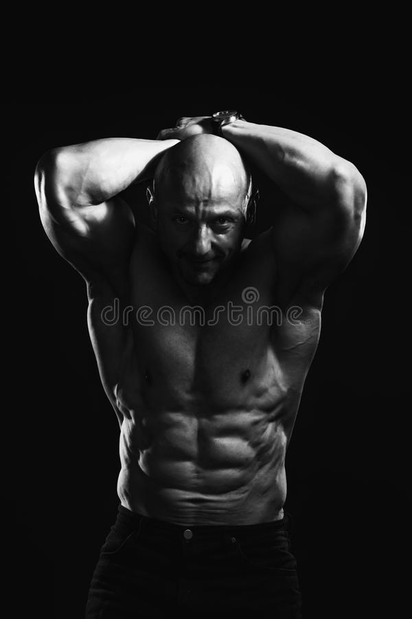 Black and white portrait of bald shirtless male bodybuilder with perfect six pack prompting to sport and training. Black and white waist portrait of brutal bald stock images