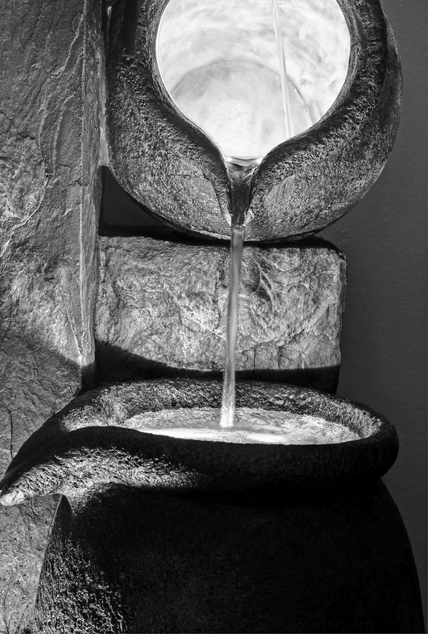 Black and White Water Pouring Forth Stone Pots. This vertical black and white photo has water pouring forth from large stone pottery containers and dramatic stock photos
