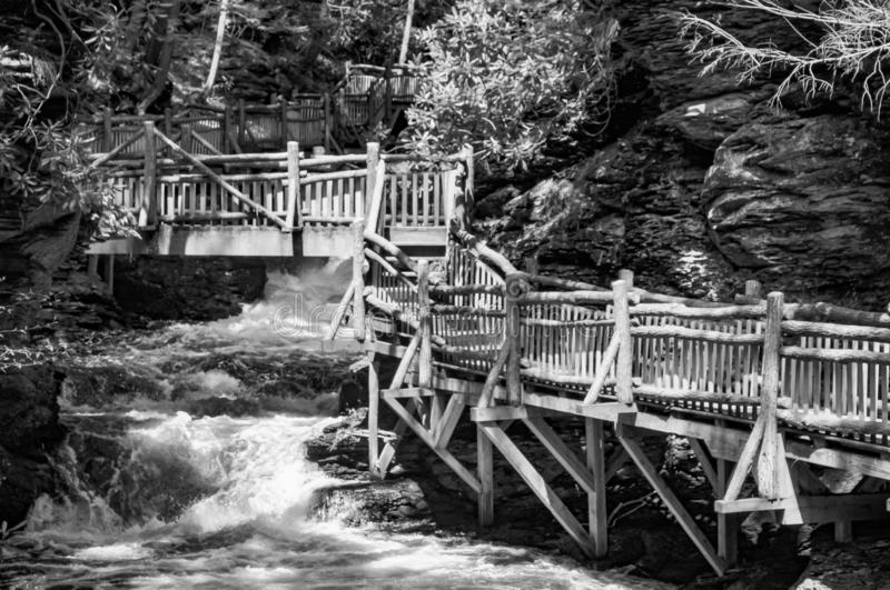 Black and White Waterfall and Wood Walkway in Pennsylvania. Black & white image of a waterfall and wood walkway through the forest in Bushkill Falls royalty free stock image